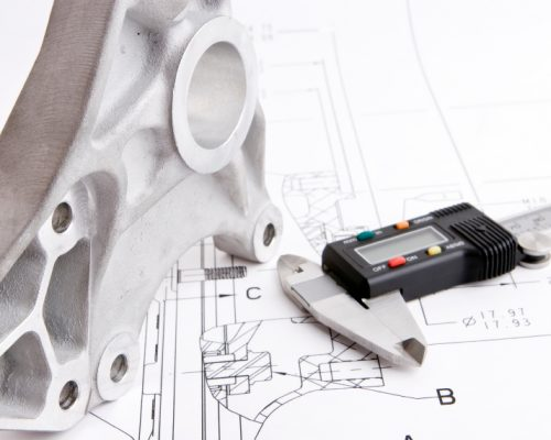 Close up of an engineering drawing with machine part and caliper.  Focus on machine part.